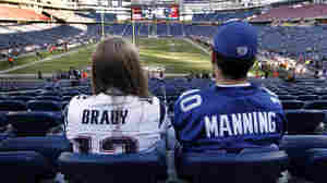 Fans in Tom Brady and Eli Manning jerseys sit before a November game between the New England Patriots and the New York Giants in Foxborough, Mass. Heading into a Super Bowl rematch, neighboring Connecticut's fans are split between the teams.