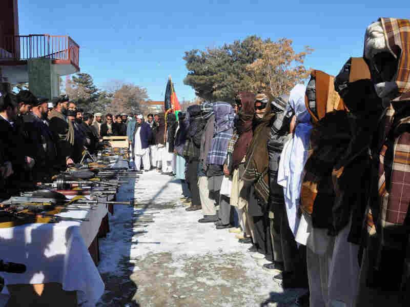 Taliban fighters stand with their weapons after joining Afghan government forces during a ceremony in Ghazni province on Jan. 16, 2012. Some 20 Taliban fighters including a key commander laid down arms and joined the peace process in Ghazni.