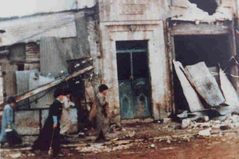 Children walk past shops that have been destroyed. On the right, it appears that the owner tied together pieces of metal and placed them in front of the entrance in an attempt to protect his shop, says Aljude.