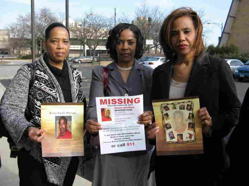 Sisters Bernice Terry (from left), Kim Dent and Sheila Hostetler hold pictures of their brother, Brian Warren, from his memorial service as well as a flier they distributed during the more than two weeks they believed he was missing.