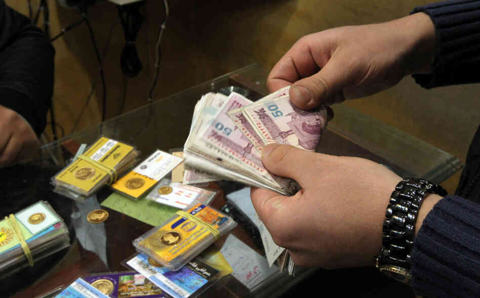 An Iranian man counts banknotes after exchanging a gold coin for cash in Tehran.