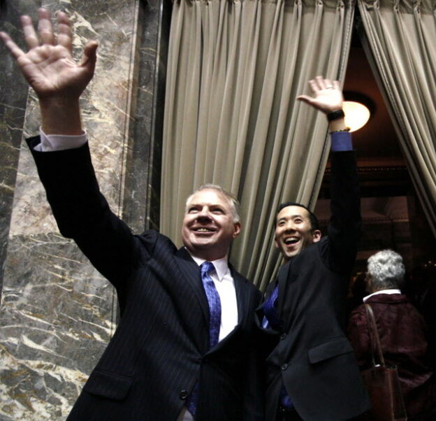 Sen. Ed Murray, D,, left, and his partner Michael Shiosaka wave at spectators in the upper gallery after the Washington state Senate voted for a proposal to legalize same-sex marriage.
