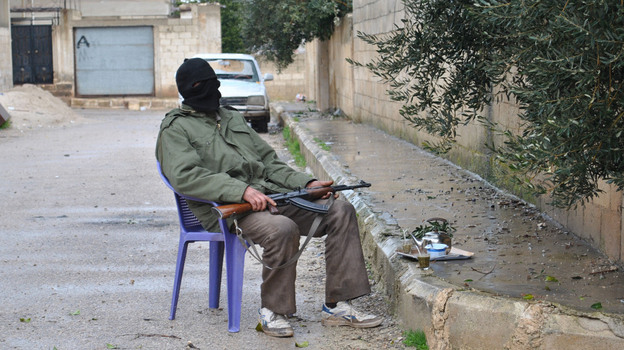 Even as the current Syrian uprising continues, some Syrians plan to mark a brutal crackdown carried out by the government 30 years ago in the central city of Hama. Here, a Syrian rebel guards an alley in the central province of Homs on Wednesday.  (AP)