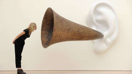 An employee poses next to an installation by US artist John Baldessari entitled 'Beethoven's Trumpet (With Ear)' at the Saatchi Gallery in central London on May 26, 2011.