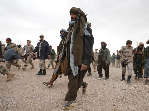 Taliban fighters walk with their weapons after joining Afghan government forces during a ceremony in Herat province, last month. Thirty fighters left the Taliban to join government forces in western Afghanistan. The Taliban announced recently that they would open a political office in Qatar ahead of talks with Washington.