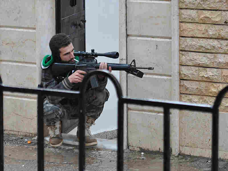 A Syrian rebel aims his weapon during a battle with the Syrian government forces at Rastan area in Homs province, central Syria, on Jan. 31.