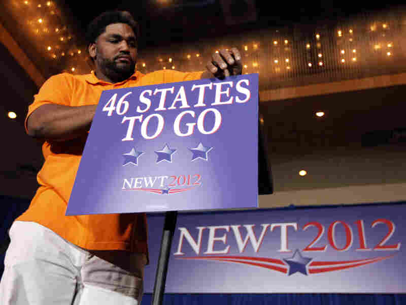 A worker mounts a sign to the podium before Republican presidential candidate Newt Gingrich's Florida Republican presidential primary night rally, Jan. 31, in Orlando, Fla.