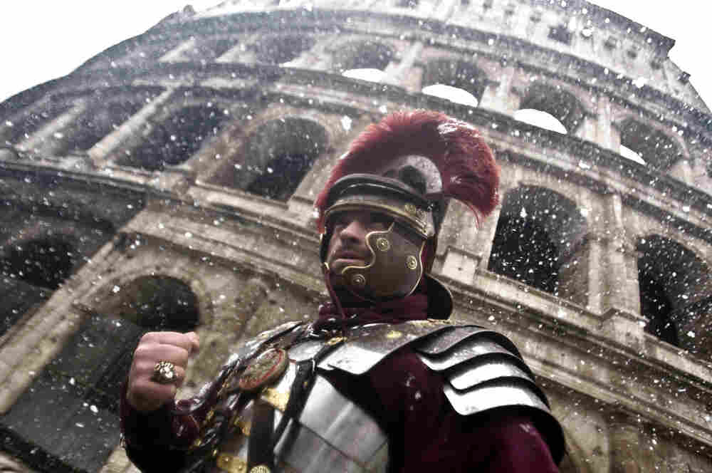 A man dressed as a Roman Centurion stands in front of the ancient Colosseum as snowflakes fall in downtown Rome on Friday.