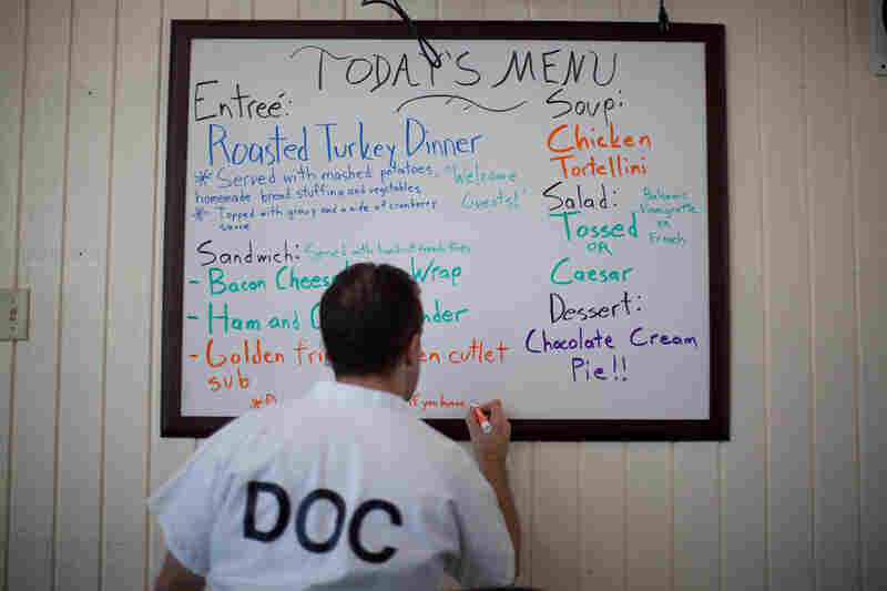 Inmate Mark Molina writes out the lunch menu for customers.