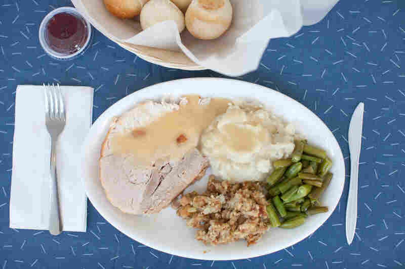Roasted turkey is served with mashed potatoesand gravy, homemade bread stuffing and vegetables, and a side of cranberry sauce.