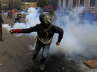 In Cairo earlier today, a masked Egyptian protester prepared to throw back a tear gas canister fired by security forces.
