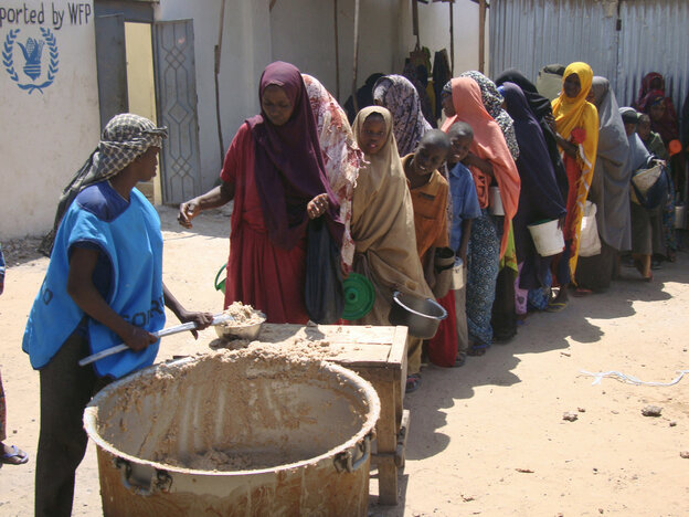 Displaced families line up to receive food rations at a feeding center in Somalia.