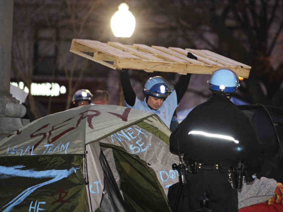 A U.S. Park Police officer removes a wooden structure from an Occupy D.C. protester's tent at McPherso