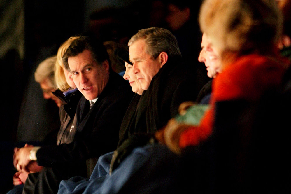 Romney chats with President George W. Bush during the Opening Ceremony at the Salt Lake City Winter Olympic Games in 2002.