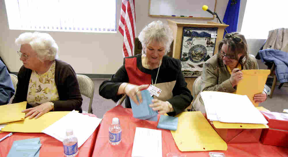 Jan White, left, Brenda Robertson, center, and Janet Freixas, right, count paper ballots at the headquarters of the Douglas County Republican Party Saturday in Minden, Nev., following county-wide Nevada caucus meetings.