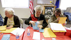 Jan White, left, Brenda Robertson, center, and Janet Freixas, right, count paper ballots at the headquarters of the Douglas County Republican Party Saturday in Minden, Nev., following county-wide Nevada