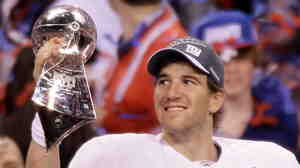 New York Giants quarterback Eli Manning holds the Vince Lombardi Trophy after the NFL Super Bowl XLVI game against the New England Patriots, Sunday (Feb. 5, 2012).