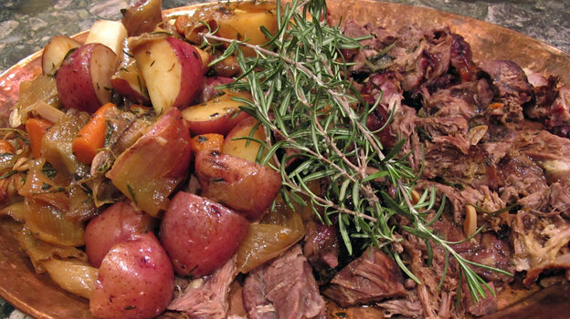 A copper platter holds braised goat meat and potatoes, garnished with rosemary