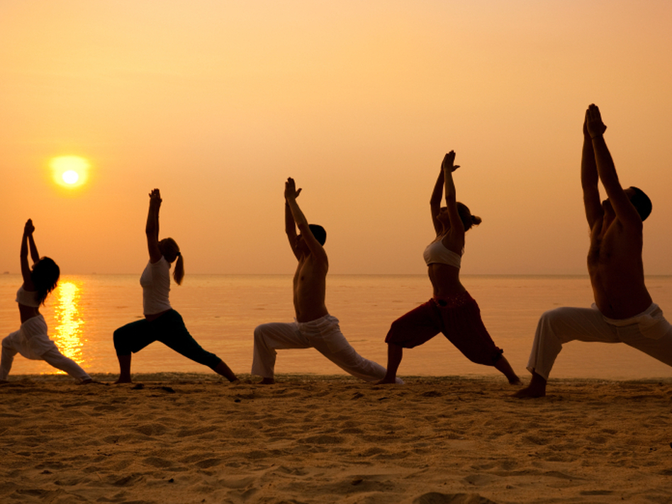 Five people on a beach stand in the warrior pose. (iStockphoto.com)