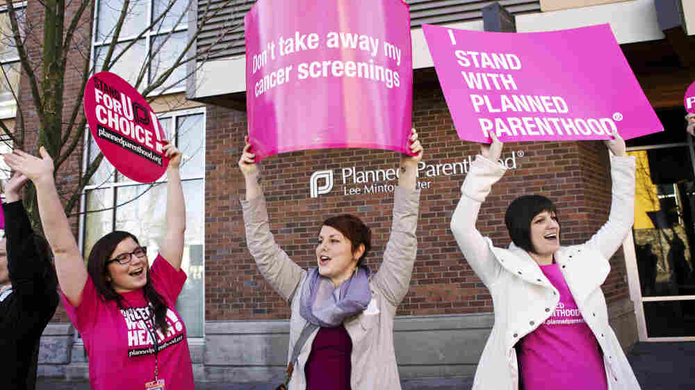 Aurora Jewell, Mandi Moshay and Kirsten Dees (left to right) hold up signs following a press conference by U.S. Sen. Patty Murray (D-WA) outside at a Planned Parenthood Clinic in Seattle, on Feb. 3.