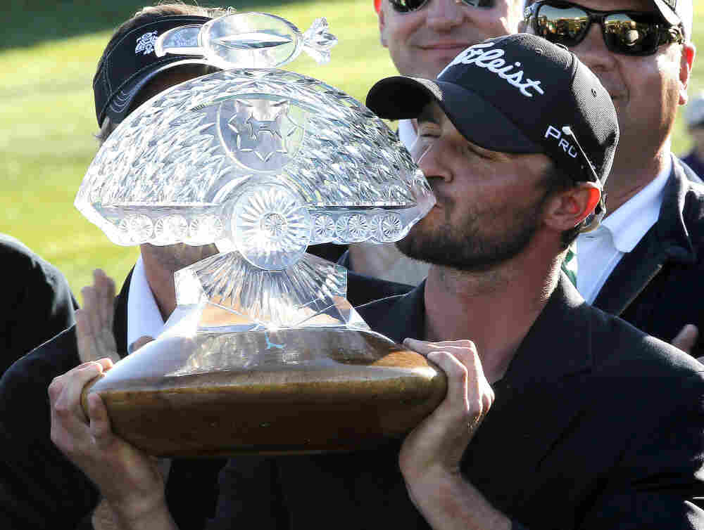 Tournament winner Kyle Stanley kisses the championship trophy after the final round of the Phoenix Open golf tournament on Sunday.