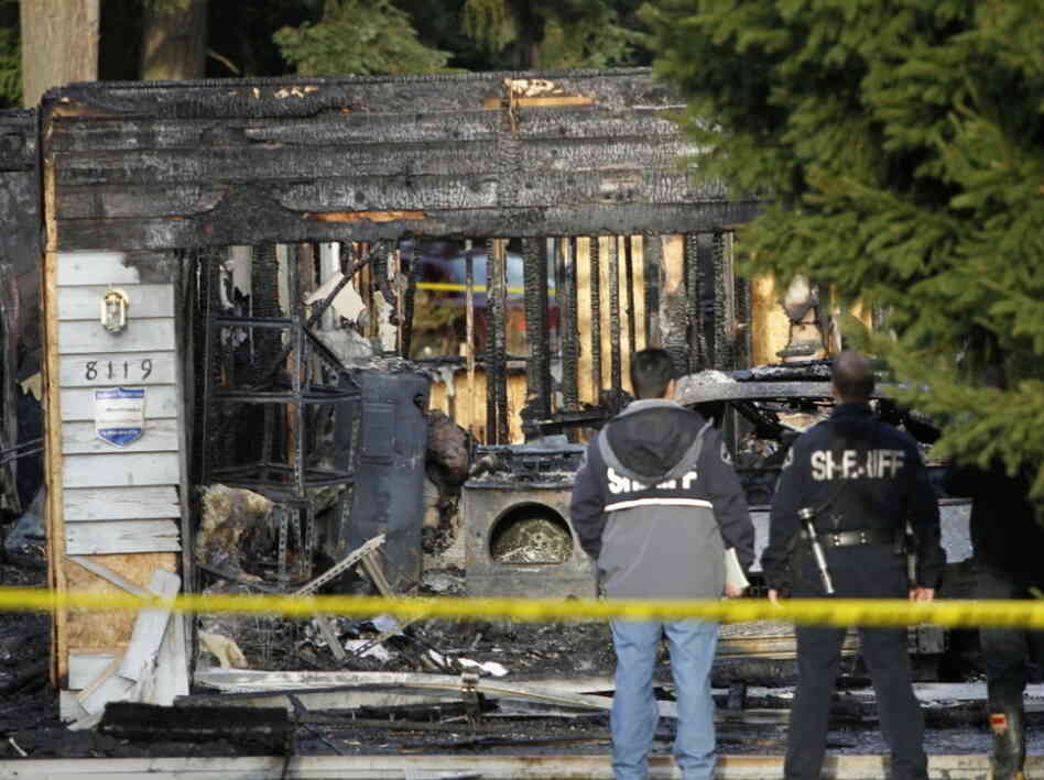 Investigators work around the smoldering remains of the house near Graham, Wash., on Sunday (Feb. 5, 2012).