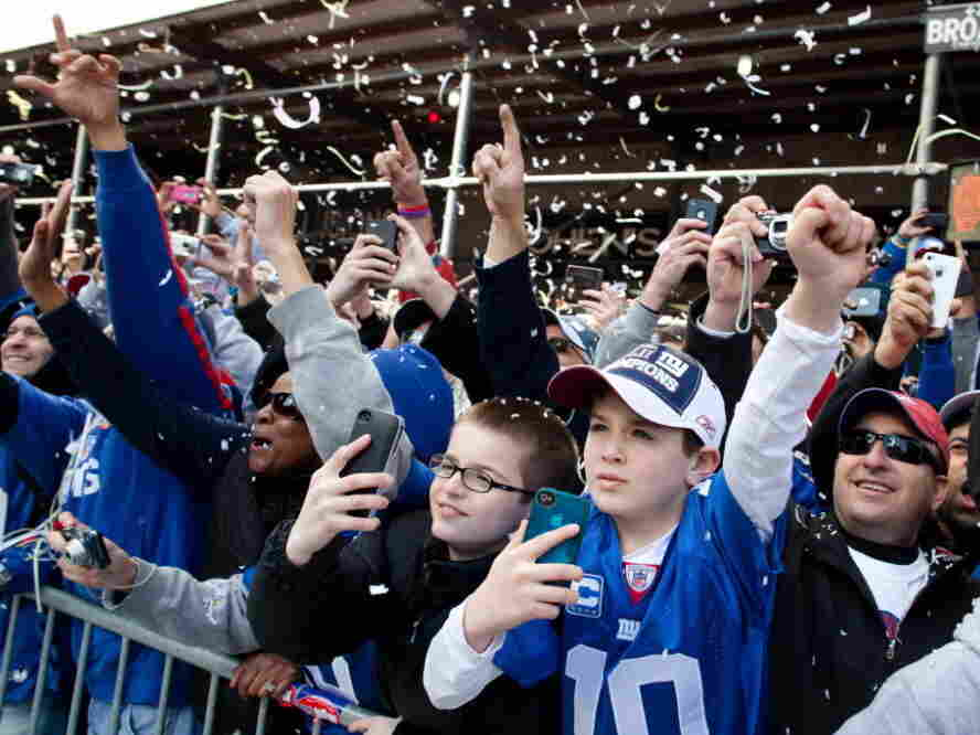 As the paper falls, New York Giants fans cheer during today's parade in Manhattan.