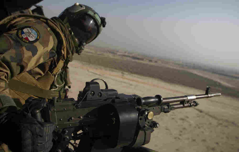 A French gunner mans a machine gun in a Puma helicopter as it flies over Afghanistan. French President Nicolas Sarkozy recently ordered the withdrawal of all French troops from the country a year ahead of schedule.