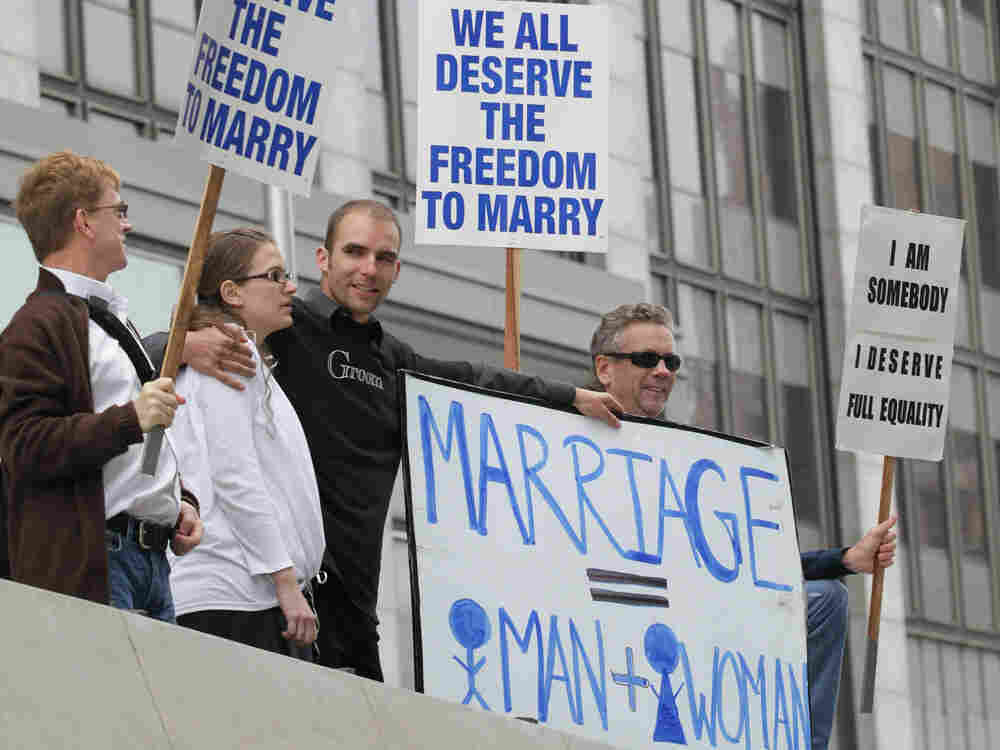 Prop 8 supporters Nadia Chayka (2-L) and her fiance Luke Otterstad (3-L) stand in between Prop 8 opponents Billy Radford (R) and Ron Weaver (L) as they stand outside of the Philip Burton Federal building August 4, 2010 in San Francisco, California.