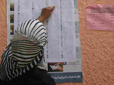 A voter checks a sample ballot outside a polling station during the second round of municipal elections in Egypt. The National Democratic Institute says it has helped mobilize volunteers and make parties aware of citizens' needs in Egypt without promoting a particular ideology.