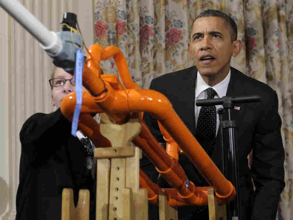 President Barack Obama helps launch a marshmallow with a gun designed by Joey Hudy, left, of Phoenix, Ariz., during the White House Science Fair.