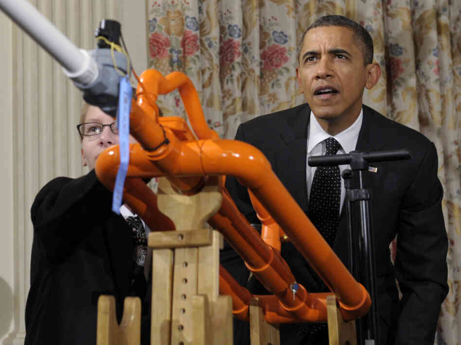 President Barack Obama helps launch a marshmallow with a gun designed by Joey Hudy, left, of P