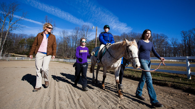 Ryan Shank-Rowe, 9, takes part in a therapeutic riding program at Little Full Cry Farm in Clifton, Va., last month.  (NPR)