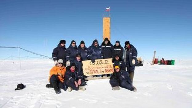In Antarctica, Russian scientists posed at the site where they say they've drilled through to Lake Vostok. The sign indicates that the breakthrough happened on Feb. 5, 2012. (Russia's Federal Service for Hydrometeorology and Environmental Monitoring)