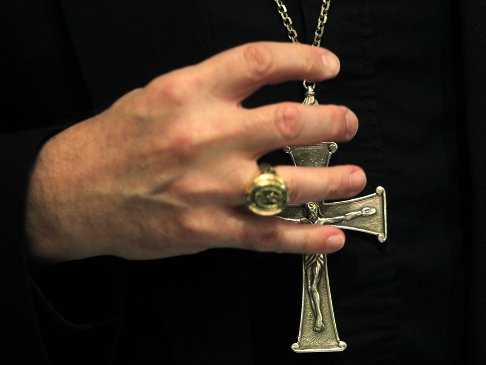 A bishop grasps his pectoral cross during the United States Conference of Catholic Bishops in Baltimore on Nov. 14, 2011.