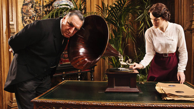 Listen Carefully: Some phrases have made it into Downton Abbey that are a little ahead of their time. Above, Mr. Carson (Jim Carter) tries out a newfangled gadget with Lady Mary (Michelle Dockery).  (Courtesy Carnival Film & Television Limited/Masterpiece)