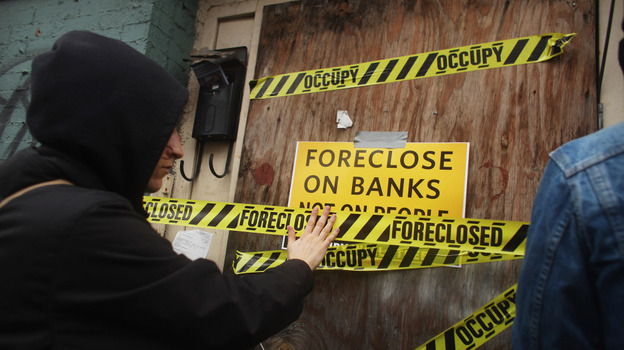 A member of the Occupy Wall Street movement places tape over a window of a foreclosed home during a march in the impoverished community of East New York in Brooklyn in December.  (Getty Images)