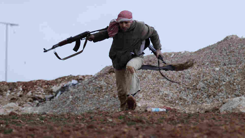 A Syrian rebel runs for cover during an exchange of fire with army troops in Idlib, Syria.