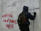 Protesters write on the wall of the National Bank of Greece during a demonstration involving thousands in Athens on Friday.