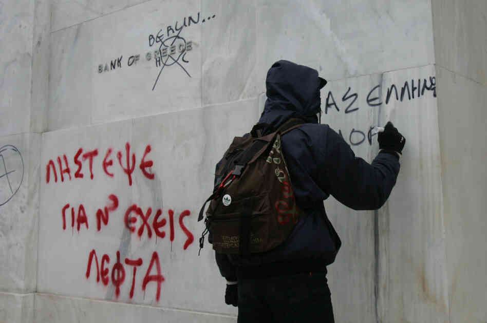 Protesters write on the wall of the National Bank of Greece during a demonstration involving thousands in Athens on Friday