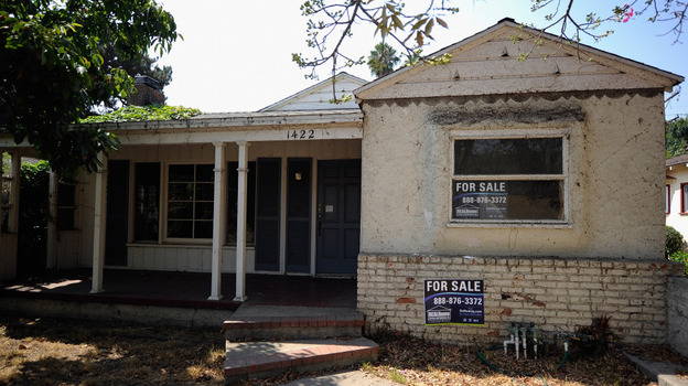 For sale signs on a foreclosed house in Glendale, Calif., last September. (Getty Images)