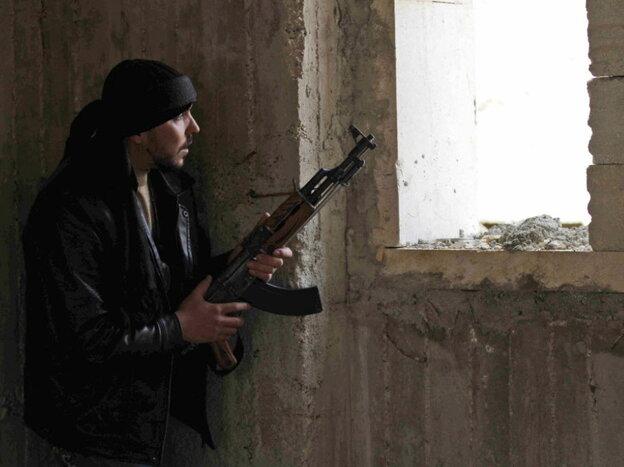 An anti-regime fighter peered  through a window in Idlib, Syria, on Thursday (Feb. 9, 2012).