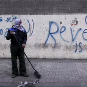 A municipal worker cleans a sidewalk Tuesday at the site of recent clashes between protesters and security forces near the Interior Ministry in Cairo