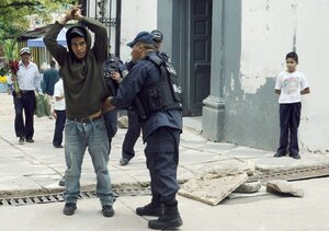 A police officer frisks a man as part of Operation Lightning, an initiative that seeks to stop violence in Honduras, in Tegucigalpa, on Nov. 1.