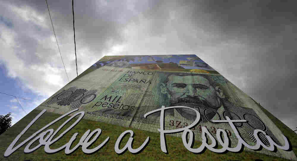 "A poster reading ""The peseta is back"" stands in Salvaterra de Mino, northwestern Spain. Some areas in Spain are returning to their former currency to make extra cash during the debt crisis."