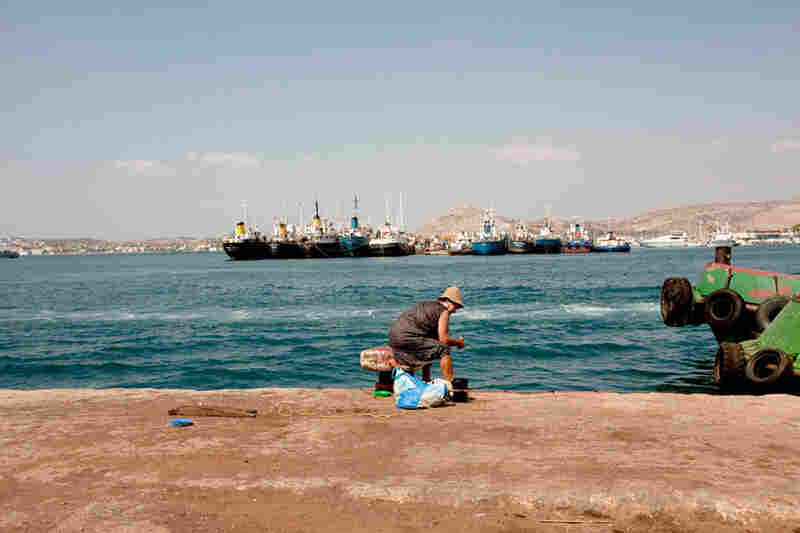 A woman fishes off the Perama coast. The ships behind her, waiting for repair, have been abandoned.