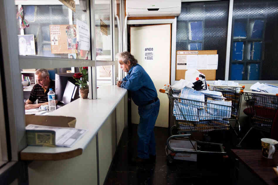 A man waits at a window at Athens' central tax office, which is filled with shopping carts full of tax papers left to be filed.