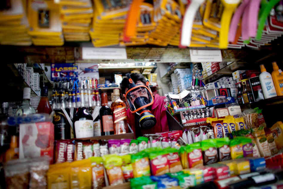 A kiosk owner wears a gas mask during anti-austerity protests outside parliament in Athens last June.