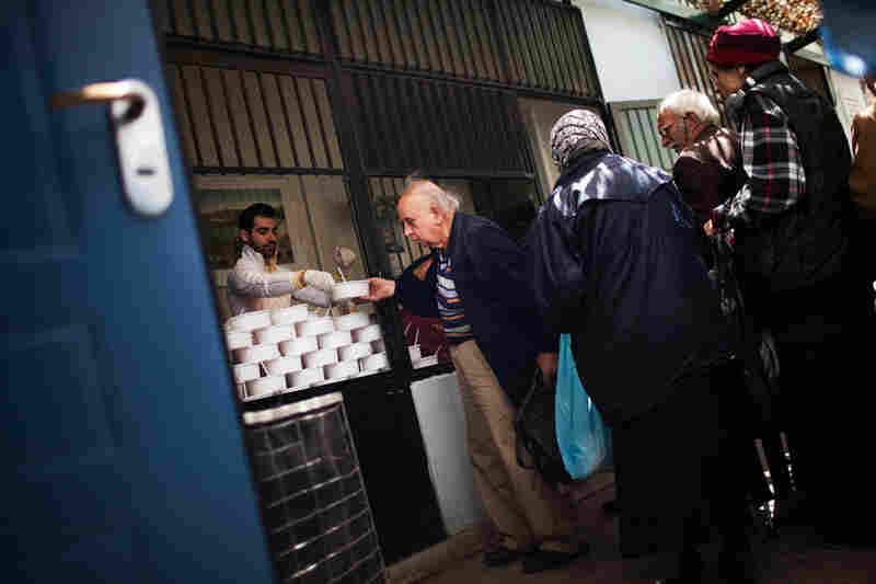 People line up for food at the Athenian Municipal Solidarity Center, which provides three daily meals for the homeless. The face of homelessness has changed in Greece, as white-collar workers have increasingly lost their jobs and require psychological support, food and shelter.