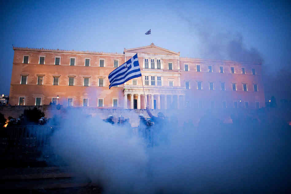 A protester holds up a Greek flag in front of the parliament building during anti-austerity demonstrations in Athens last summer.